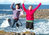 Students jumping for a picture at the beach