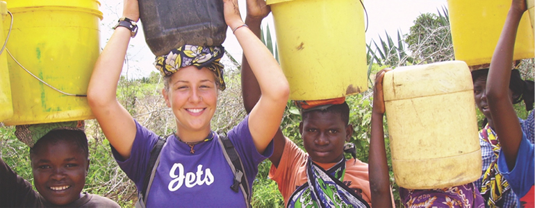 fetching water with her host family in Kenya