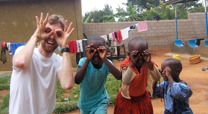 An artist with kids in Rwanda.