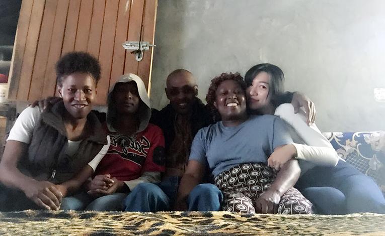 International volunteer with host family in Kenya