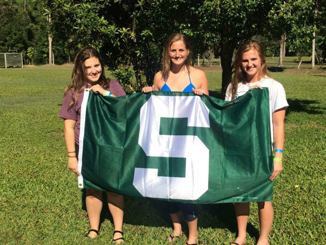 Students holding a Michigan State Flag
