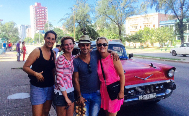 Friends posing together on a street in Cuba