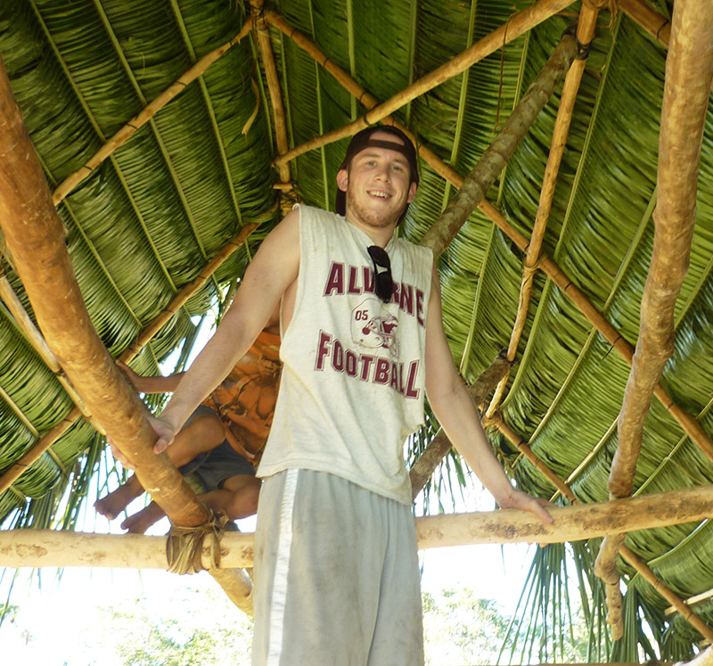 International student posing under a thatched roof in Belize.