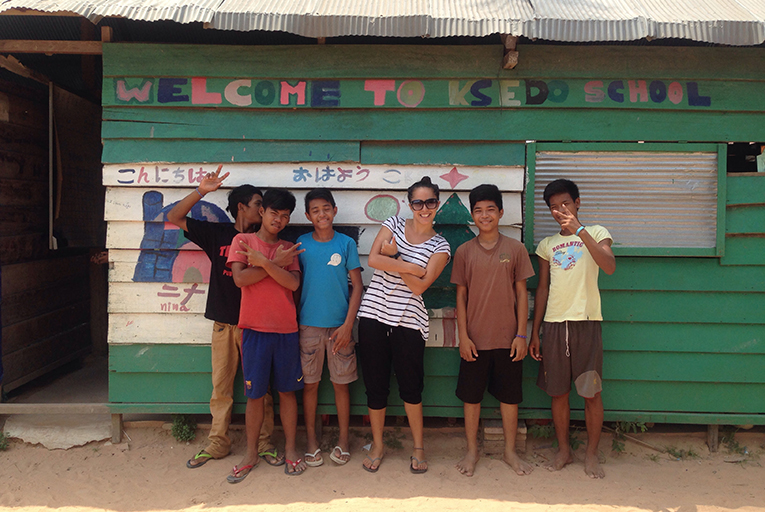 International teacher with local students outside Ksedo School in Cambodia
