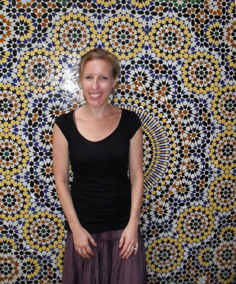 Girl standing in front of a mosaic tile wall