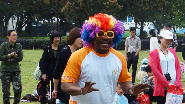 Man with a rainbow wig on in a park in China