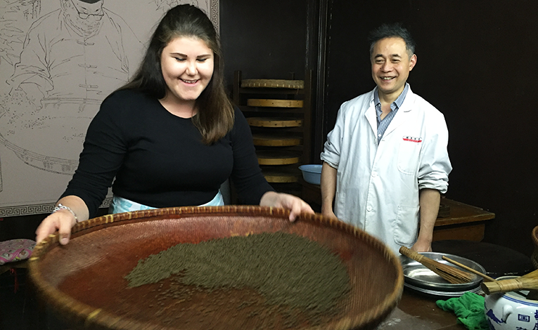 Tourist learning how to make traditional Chinese medicine
