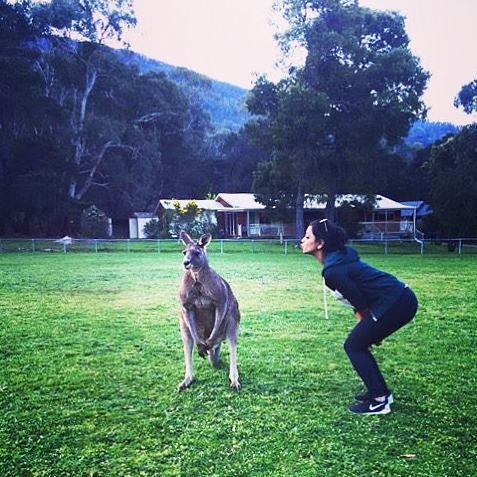 Girl standing by a kangaroo in Australia