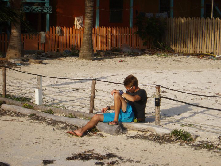 Man sitting in the sand at a beach in Belize