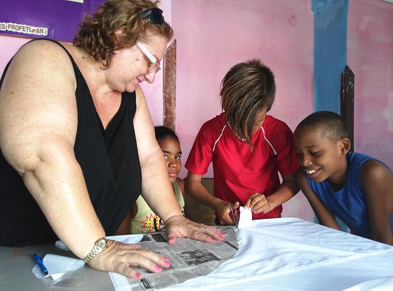 Volunteer in Cuba teaching students how to sew