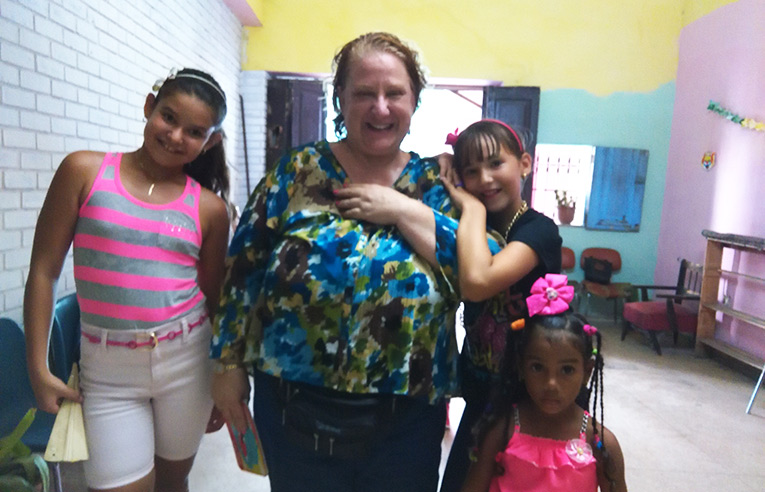 International volunteer with local kids in Cuba