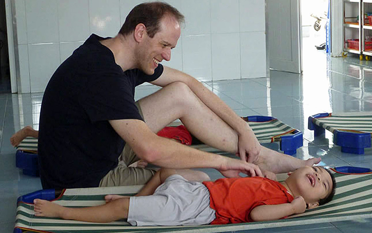 Volunteer tickling an orphan in Ho Chi Minh City, Vietnam