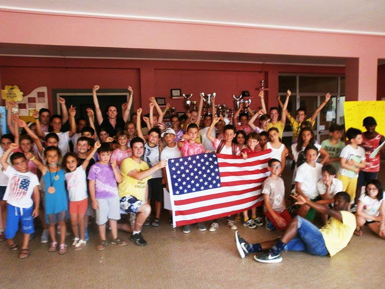 English teachers and Italian students holding an American flag