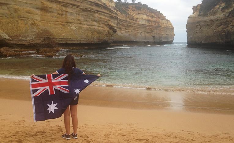 Girl holding the Australian flag at Loch Arg Gorge alongn the Great Ocean Road in Australia