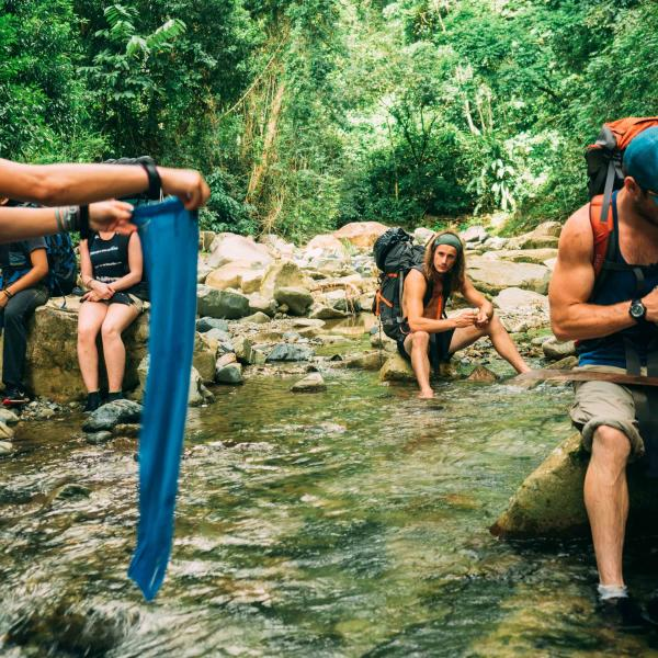 Outdoor Recreation students stop to rest at a river crossing during a program hike throughout the jungle