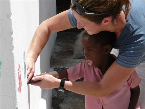 a volunteer helping a child print his hands on the wall