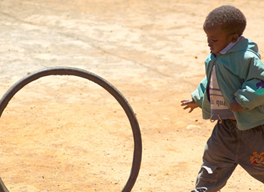 A child rolling a bicycle wheel