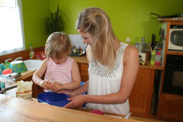 mother teaching daughter how to make a cake