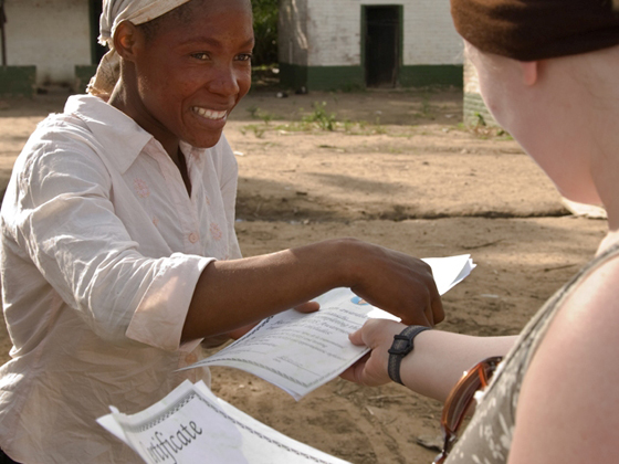 A volunteer giving a paper to an African native