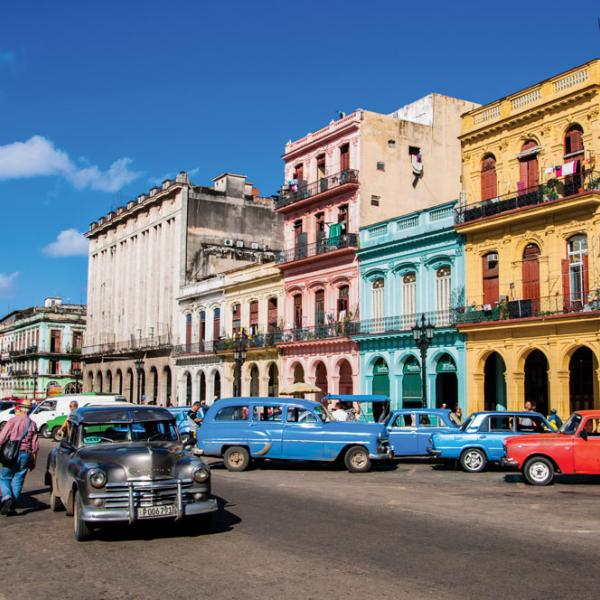 Pedestrians in Cuba stroll along a street lined with colorful cars