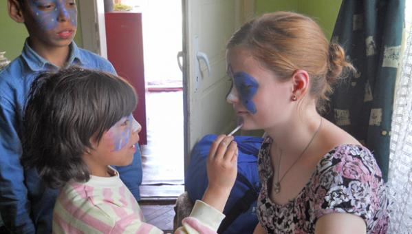 a child putting paint on the face of a volunteer