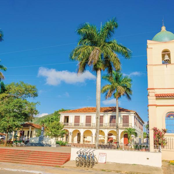 Beautiful Spanish style building with blue skies and palm trees in Cuba