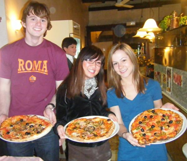Students learning to make pizza at a local pizzeria