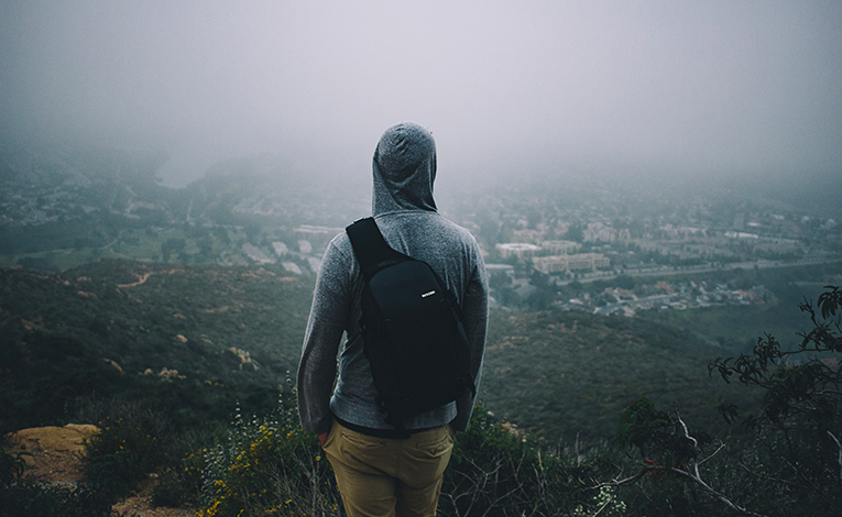 Man looking out over a foggy city