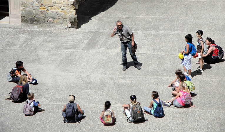 Students sitting in a semi-circle around their instructor outside
