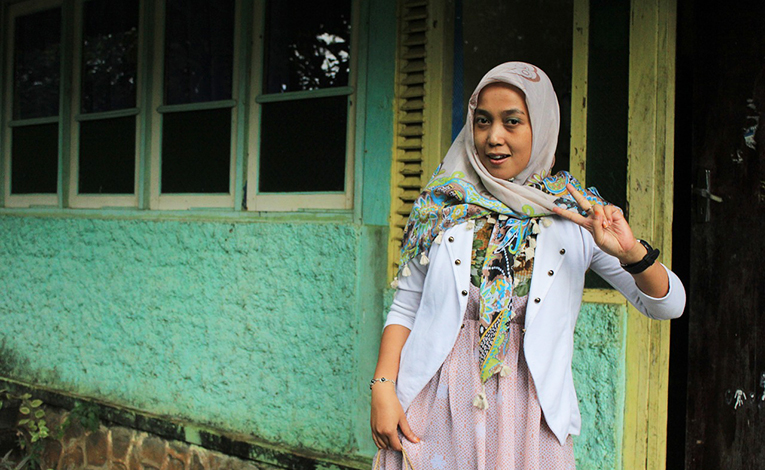 A woman wearing a hijab doing the peace sign