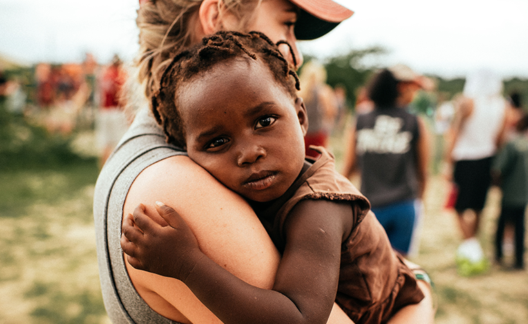 Portrait of a young girl being held by a volunteer