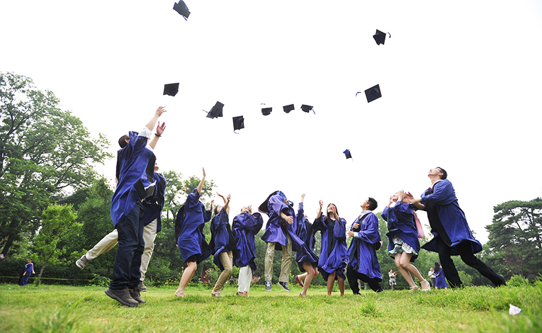 Students throwing graduation caps into the air