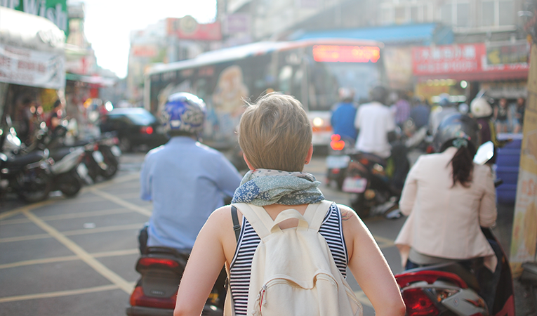Girl walking through a busy street in Asia