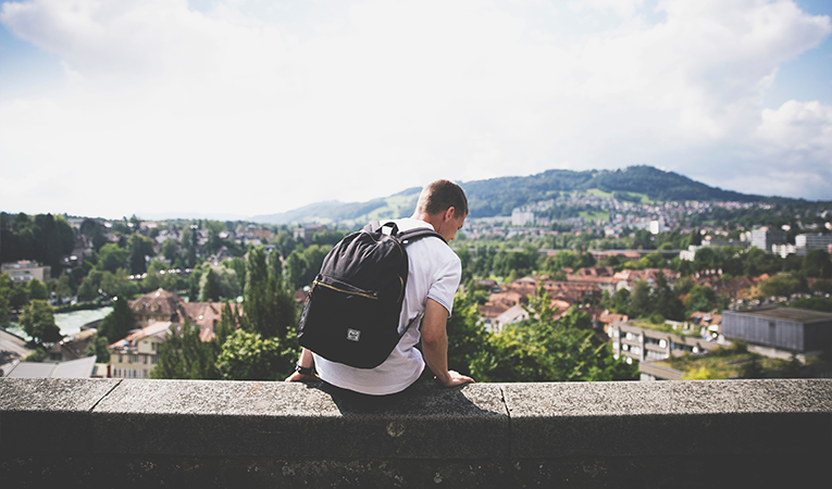 Person sitting on a ledge, overlooking a city