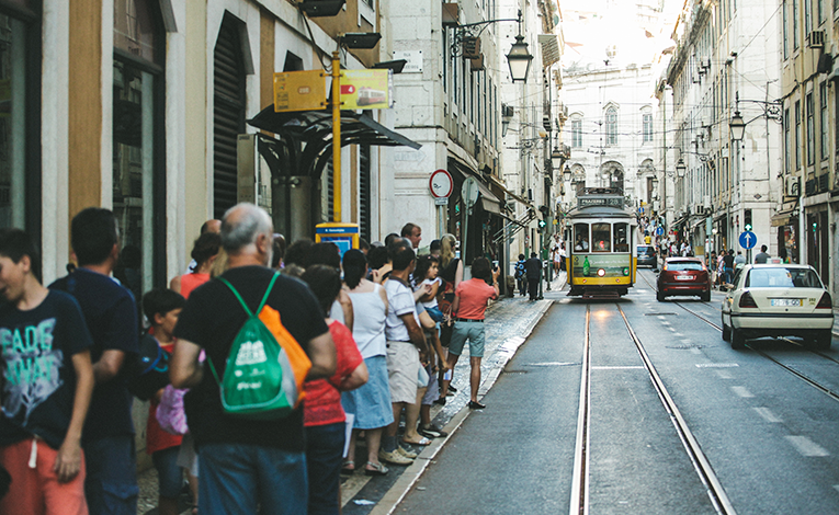 large group of people waiting at a tram stop in Lisbon, Portugal as a street car approaches