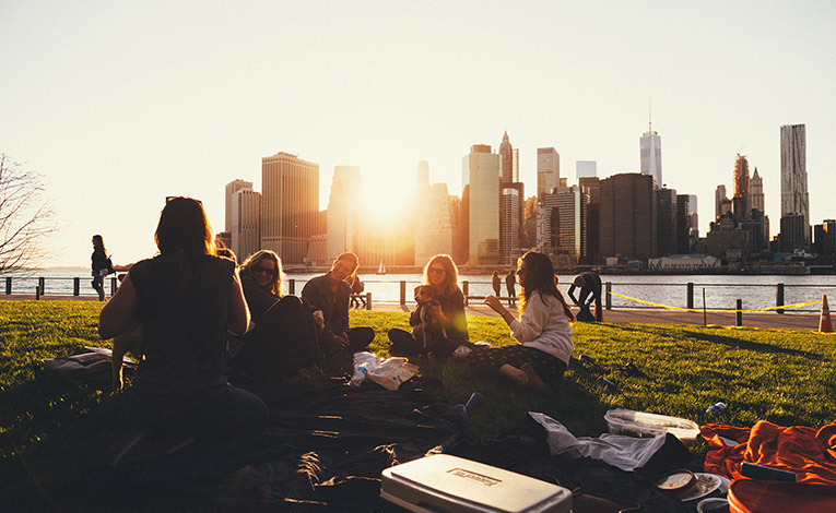 Friends sitting in the grass at a riverside park at sunset