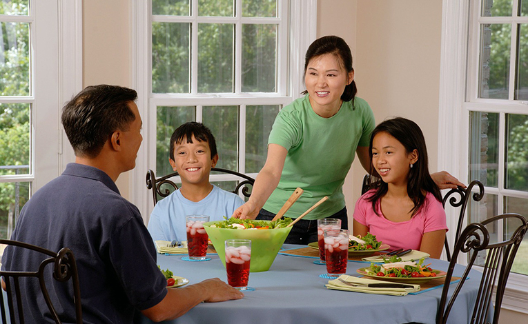 Man eating dinner with host family at table