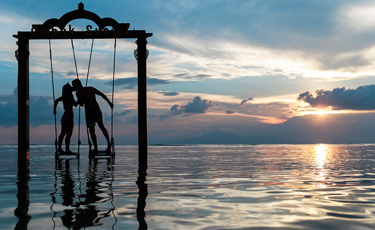 Silhouette of a man and woman kissing on swings over water