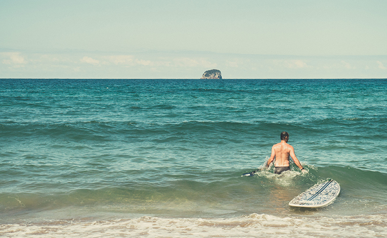 Man in the ocean with a stand up paddle board