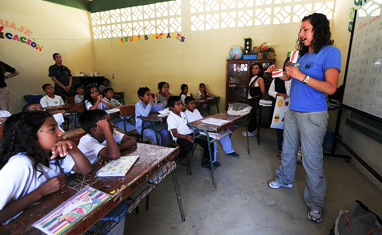 Woman teaching in front of classroom.