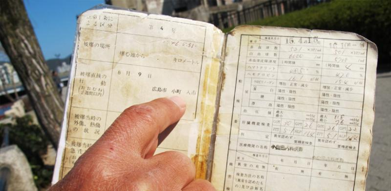 Nuclear bomb survivor Mito Kosei points to his techo, the Japanese document that confirms he is an atomic bomb survivor. Kosei was in his mothers womb during the bombing and now speaks out against both nuclear weapons and nuclear energy.