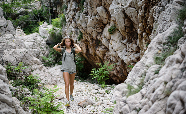Baska, Croatia woman hiking through rock formations