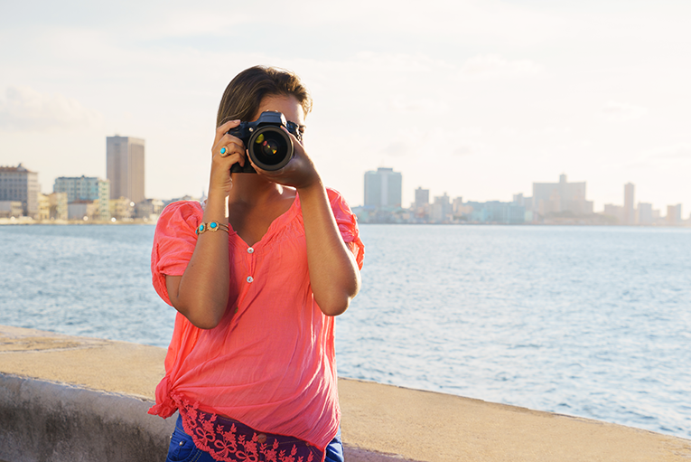 Girl taking a photo on the Malecon in Havana, Cuba
