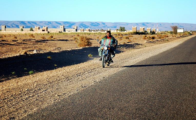 Man riding a motorcycle through Moroccan desert.