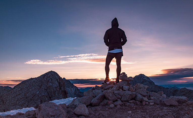 Hiker triumphant at summit of mountain during sunset