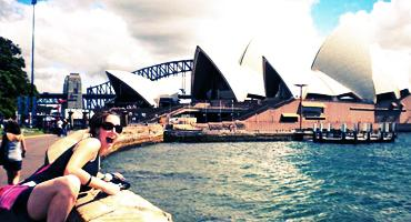 A volunteer poses in front of the Sydney Opera House, one of Australia's most famous landmarks