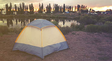 A tent by the side of a lake.