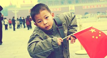 A Chinese boy carrying a flag