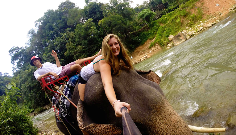 A man and a woman on an elephant ride