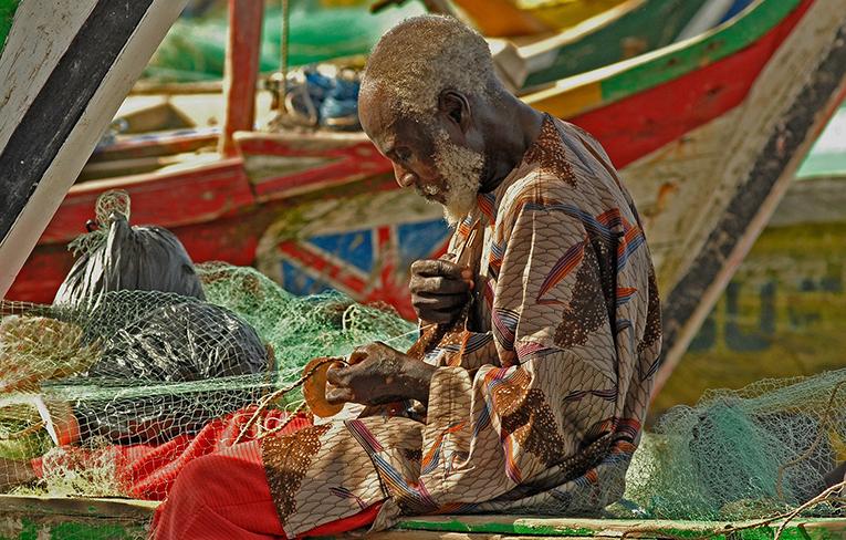 African man weaving at a market